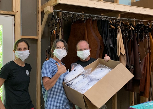 Trish Bender accepting masks from Michael and Marie Williams